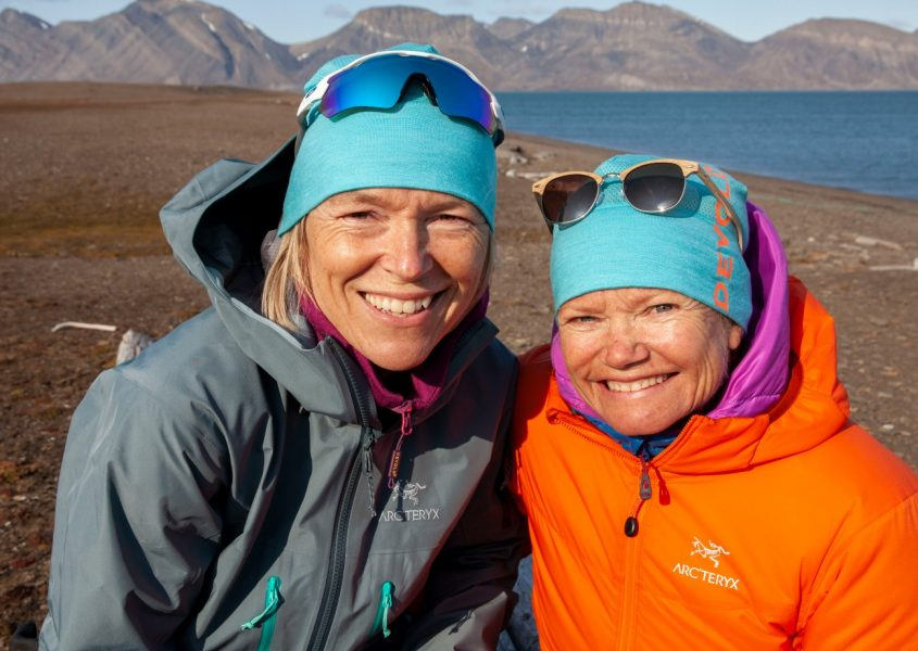 Two Arctic explorers in brightly coloured outdoor clothing