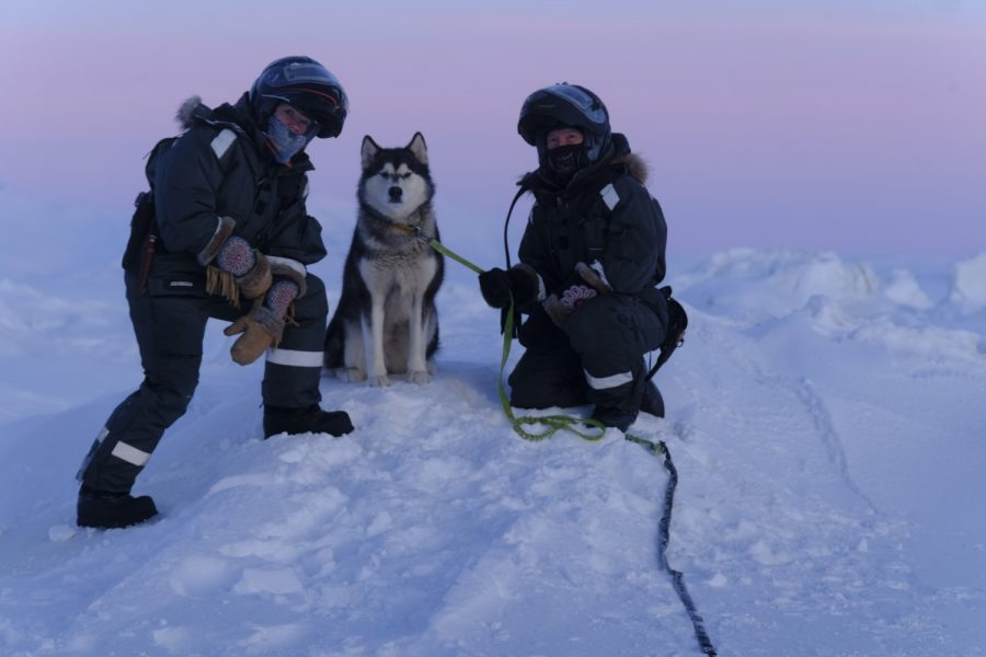 Two female Arctic explorers and their husky in the snow