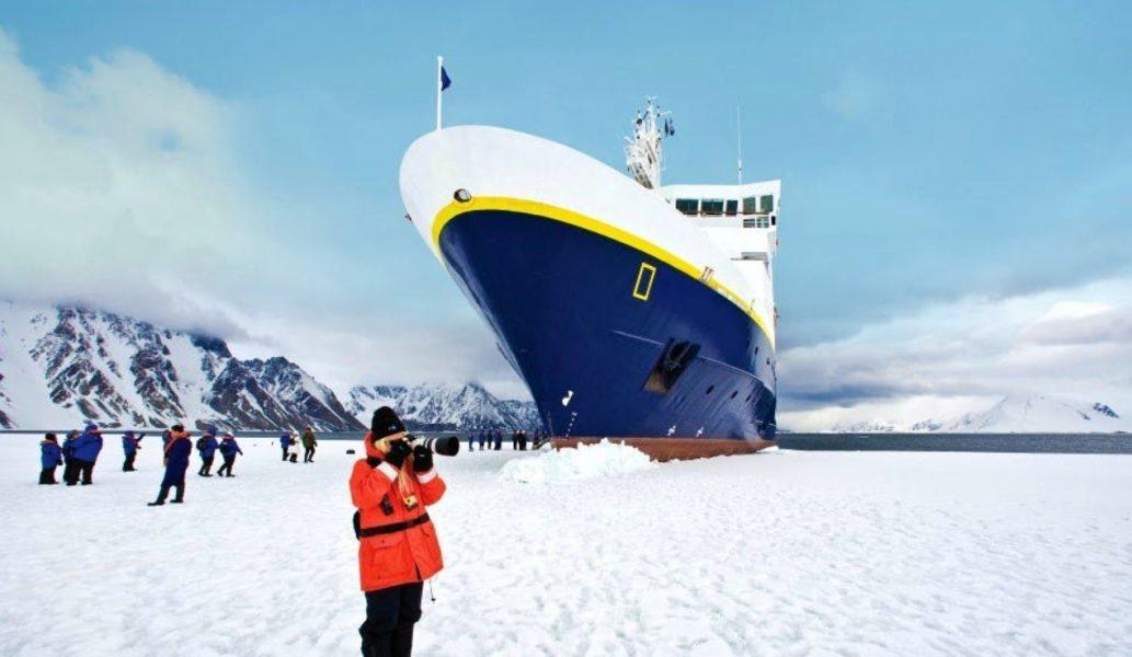 An explorer on the Antarctic ice below a large ship © Michael S Nolan